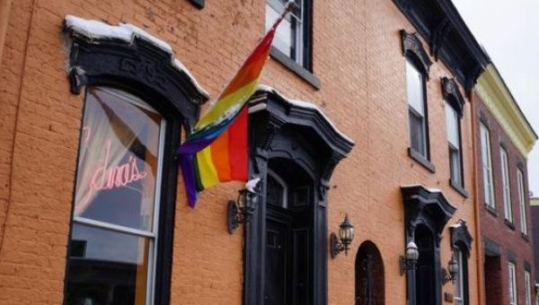 A rainbow flag hangs waves outside Edna