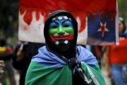 An Indigenous Mapuche activist wears a Guy Fawkes mask painted with the Mapuche flag during a protest march by Mapuche Indian activists against Columbus Day in downtown Santiago, Chile, October 12, 2015.