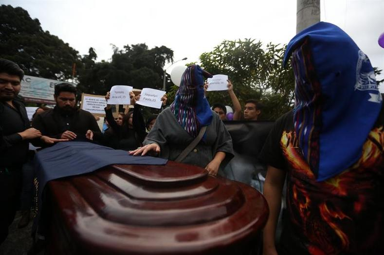 In Guatemala City, protesters carry a coffin to represent the victims of the fire and holds signs with the names of the 40 girls who died.