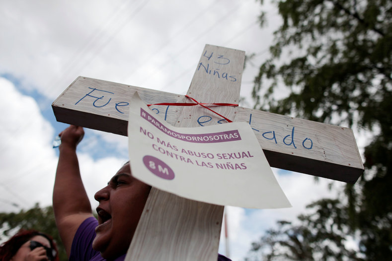 "An activist holds a cross with a sign that reads ""No more sexual abuse against girls"" during a protest outside of Guatemala"