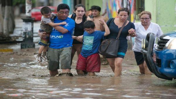 Residentes cruzan una calle inundada en Trujillo, al norte de Perú.