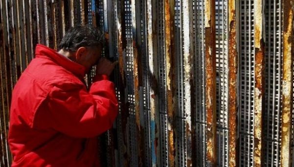 A man talks to relatives at a wall separating Mexico and the United States, as photographed from Playas Tijuana, in Tijuana, Mexico.