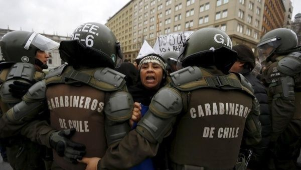 Mapuche activists try to get through riot police during a demonstration in Santiago, Chile Aug. 27, 2015, after truckers from the south arrived in the city.