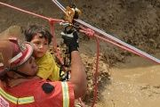 Residents of the Huachipa populous district are helped by police and firemen rescue teams to cross over flash floods.