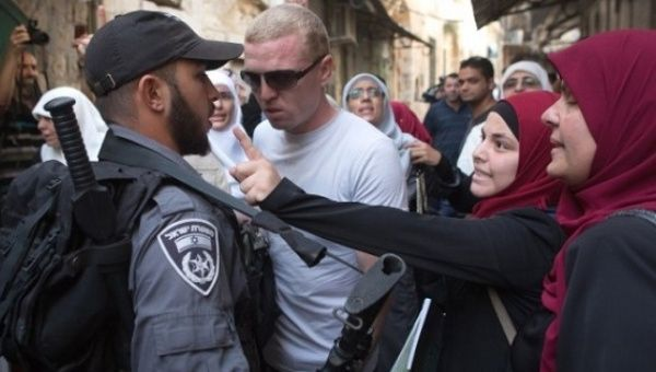 Palestinian women argue with Israeli policemen during a protest at the Temple Mount in Jerusalem, Sept. 16, 2015.