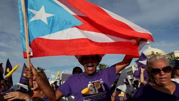 A member of a labor union shouts slogans while holding a Puerto Rico flag during a protest in San Juan Sept. 11, 2015.