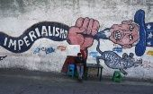 Man sits by a graffiti denouncing U.S. imperialism in Caracas.