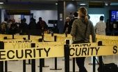 Passengers make their way through a security checkpoint at the JFK International airport in New York, Oct. 11, 2014.