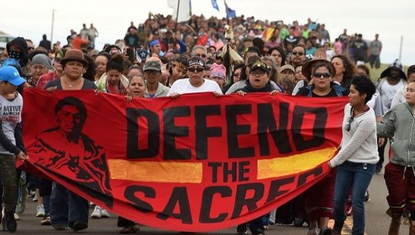 Native Americans march to a sacred burial ground site they say was disturbed by bulldozers building the Dakota Access Pipeline