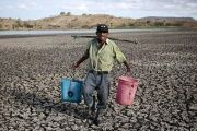 A farmer carries buckets of water in Palyitas town, Nicaragua, March 3, 2016.