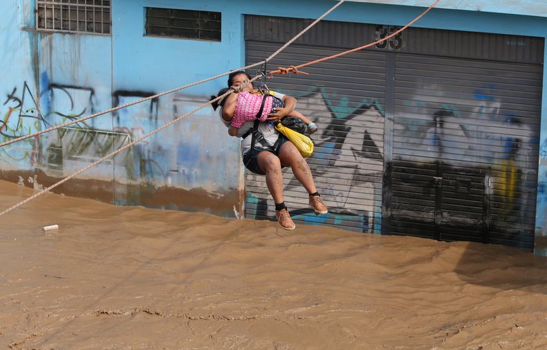 A woman and a child are evacuated with a zip line after the Huayco river flooded its banks sending torrents of mud and water rushing through the streets in Huachipa.