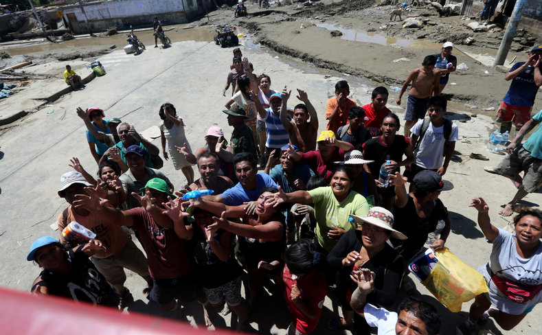 Flood survivors wait for food after rivers breached their banks. A sudden and abnormal warming of Pacific waters off Peru has unleashed the deadliest downpours in decades, with landslides and raging rivers sweeping away people, clogging highways and destroying crops.