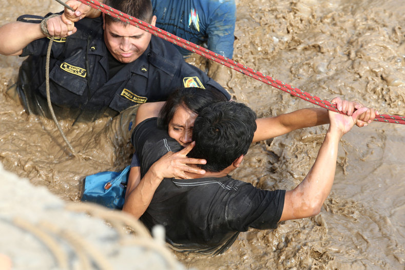 A woman is assisted while crossing a flooded street after the Huayco river flooded its banks.