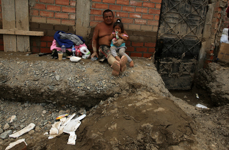 A man holding a child sits on a street. Bridges have collapsed as rivers have breached their banks, and cows and pigs have turned up on beaches after being carried away by rivers.