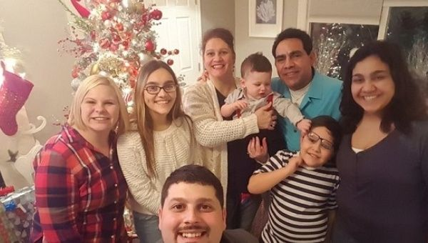 Trump supporter Helen Beristain (C) holding her grandchild is shocked her husband Roberto (R-blue shirt) will be deported