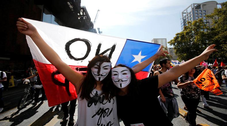 """Al ritmo del sonido de contagiosos tambores, portando banderas chilenas y afiches, los manifestantes corearon la consigna """"NO+AFP""""."""