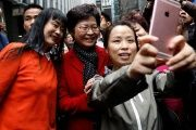 People take selfies with Carrie Lam, chief executive-elect, a day after she was elected in Hong Kong, China, March 27, 2017.