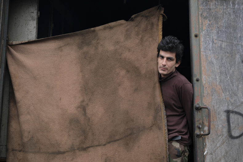 Ahmad Shakib poses for a picture at the entrance of a derelict customs warehouse in Belgrade, Serbia.