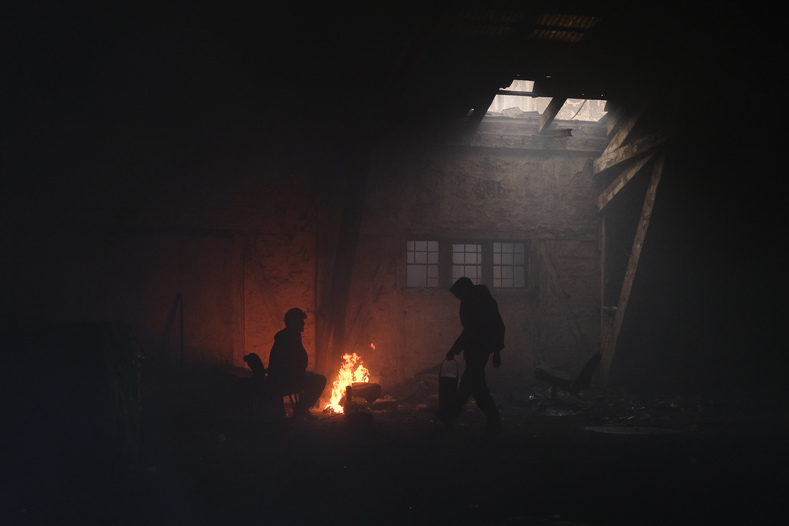 Migrants warm themselves around a fire in the abandoned warehouse where the young Ali lives.