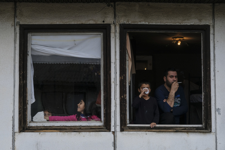 A family looks out the window of their bedroom in the refugee center where both Otra al-Khadra and Aras Mahmoud live in Belgrade.