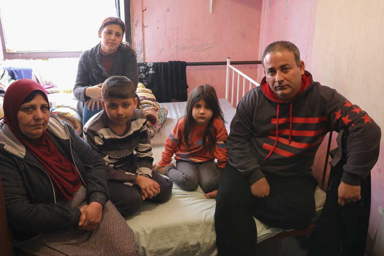 Aras Mahmoud with his wife, mother and children in their bedroom in a refugee center in Krnjaca.