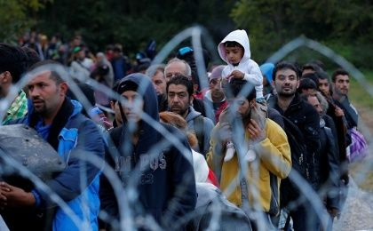 Refugees make their way after crossing the border at Zakany, Hungary, Oct. 16, 2015.