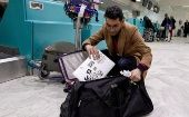 A Libyan traveler packs his laptop in his suitcase before boarding his flight for London at Tunis-Carthage International Airport.
