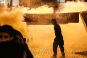 Anti-riot police throw tear gas as a man stand next to a banner reading