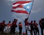 A protester waves a Puerto Rican independence flag during a protest in San Juan.
