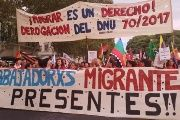 Migrant rights activists hold banners saying