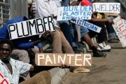 Men hold placards offering employment services in Glenvista, south of Johannesburg. Oct. 7, 2010.