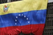 A Venezuelan flag hangs from a building near the national election board.