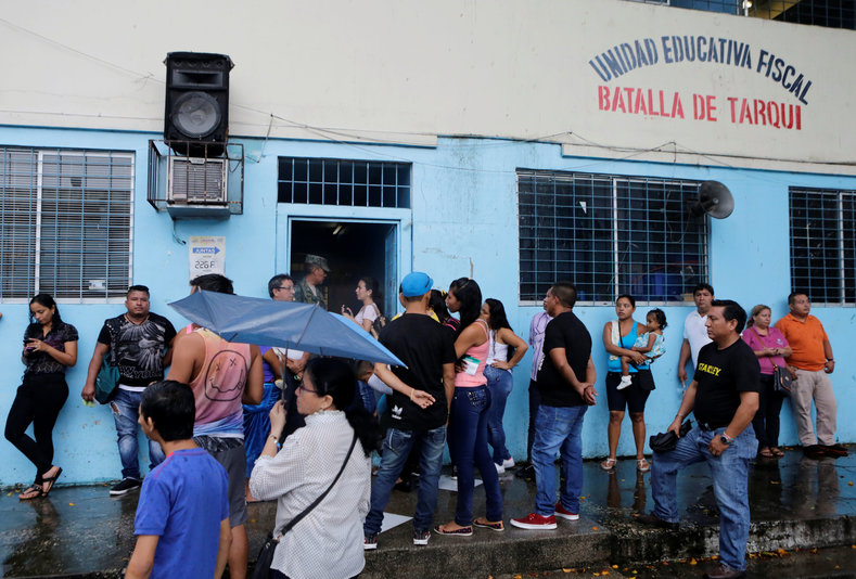People stand outside a school used as a polling station during the presidential election, in Guayaquil.