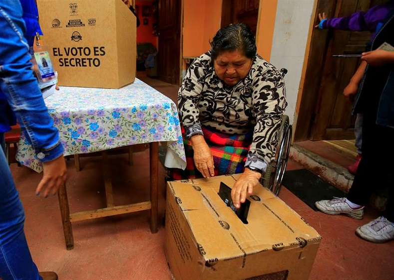 """Officials of the National Electoral Council attend the home of Margarita Guaman two days ahead of the election as part of the """"vote at home"""" services for people with disabilities."""