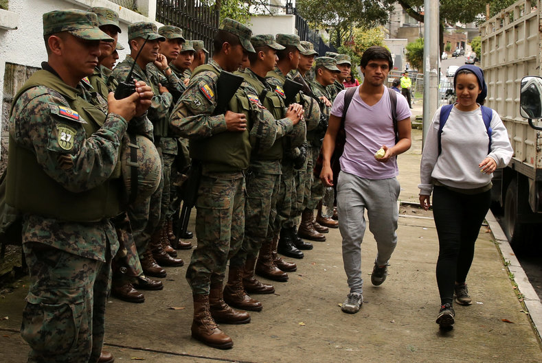 Residents walk as soldiers stand near the Electoral National Council  headquarters prior to Sunday presidential election in Quito.