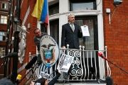WikiLeaks founder Julian Assange holds a copy of a U.N. ruling as he makes a speech from the balcony of the Ecuadorian Embassy, London, U.K., Feb. 2016.