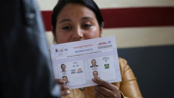An electoral worker holds up a ballot paper at a polling station during the presidential election in Quito.