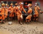 Rescue members recover a body in a house after flooding and mudslides caused by heavy rains pushed sediment and rocks into buildings in Mocoa, Colombia.