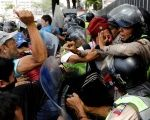 Right-wing protesters attack a Venezuelan police officer in Caracas.