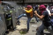 Protesters clash with police forces in Caracas on April 4, who tried to march towards the National Assembly to support the removal of TSE judges.