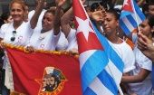 Cuban youth hold national flags and a Young Communist League banner.