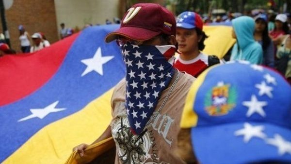 A Venezuelan opposition protester wears a U.S. flag on his face.