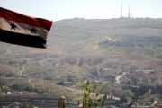 A Syrian national flag flutters as Qasioun mountain is seen in the background from Damascus, Syria April 7, 2017.
