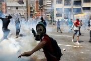 A demonstrator throws a tear gas canister back to policemen during an opposition rally in Caracas, Venezuela, April 6, 2017.