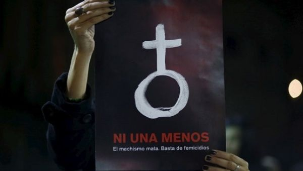 A woman holds up a poster with a female symbol during a demonstration demanding policies to prevent femicides in Buenos Aires, Argentina, June 3, 2015.