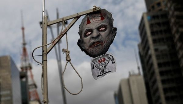 A demonstrator holds a mock gallows and a mask with a defaced picture depicting Brazil