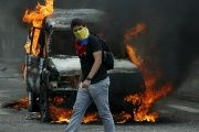 A demonstrator wearing a Venezuelan national flag to cover his face walks in front of a burning van during a protest against President Nicolas Maduro's government in San Cristobal, Venezuela, March 3, 2016.