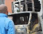 Hector Rodriguez, PSUV lawmaker, looks at a vehicle destroyed by vandals on Thursday night in Los Teques.