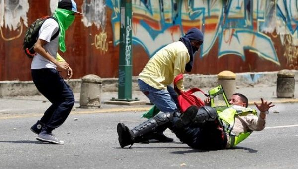 Venezuelan opposition protesters attack a police officer in Caracas.