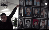 "A former educator shows the photos of teachers, who were allegedly killed by the Turkish state, to the filmmakers of the ""Erdogan"